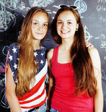 Dra tillbaka till skolan efter sommarsemestrar, två tonåriga verkliga flickor i klassrum med svart tavla som tillsammans målas, d Arkivbild