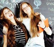 Dra tillbaka till skolan efter sommarsemestrar, två tonåriga verkliga flickor i klassrum med svart tavla som tillsammans målas, d Arkivfoto