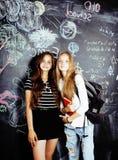 Dra tillbaka till skolan efter sommarsemestrar, två tonåriga verkliga flickor i klassrum med svart tavla som tillsammans målas, l arkivbild