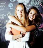 Dra tillbaka till skolan efter sommarsemestrar, tv? ton?riga flickor i klassrum med svart tavla som tillsammans m?las royaltyfri foto
