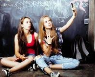 Dra tillbaka till skolan efter sommarsemestrar, tv? ton?riga flickor i klassrum med svart tavla som tillsammans m?las fotografering för bildbyråer