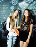 Dra tillbaka till skolan efter sommarsemestrar, tv? ton?riga flickor i klassrum med svart tavla som tillsammans m?las arkivfoto