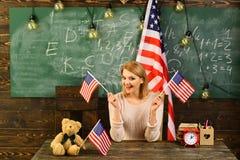 Dra tillbaka till skolan eller hem- skolgång med läraren Kvinna i klassrum med amerikanska flaggan på kunskapsdagen Patriotism oc Royaltyfria Bilder