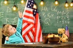 Dra tillbaka till skolan eller hem- skolgång dra tillbaka till skolabegreppet med den lilla pojken på skolan på amerikanska flagg Arkivfoton