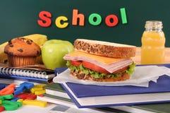 Dra tillbaka till skolan med matsäck, smörgåsen, äpplet, drinken på klassrumskrivbordet eller tabellen Royaltyfri Bild
