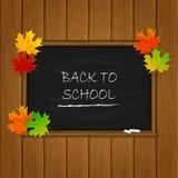 Dra tillbaka till skolan och lönnlöv på den svarta svart tavlan Arkivbild