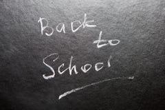 Dra tillbaka till skolan - ord på svart tavla med krita royaltyfri foto