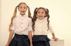 Dra tillbaka till skolan ?r h?r Sm? flickor som ?r lyckliga att vara tillbaka till skolan lyckliga flickor little arkivbilder