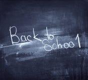 Dra tillbaka till skolan som är skriftlig på den blåa svart tavlan Arkivbilder