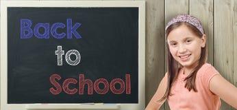 Dra tillbaka till skolan som är skriftlig på svart tavla med unga flickan royaltyfria bilder