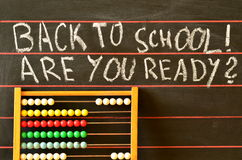 Dra tillbaka till skolan som är skriftlig på svart tavla och kulrammet Arkivbild