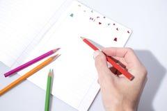 Dra tillbaka till skolan som skriver på en förskriftsbok med en blyertspenna royaltyfri bild