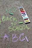 Dra tillbaka till skolan suckar skriftligt med kulöra chalks på en trottoar Dra tillbaka till skolan på en asfalt och semesterbeg Arkivbild