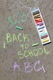 Dra tillbaka till skolan suckar skriftligt med kulöra chalks på en trottoar Dra tillbaka till skolan på en asfalt och semesterbeg Arkivfoton