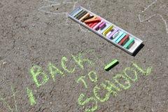 Dra tillbaka till skolan suckar skriftligt med kulöra chalks på en trottoar Dra tillbaka till skolan på en asfalt och semesterbeg Royaltyfri Fotografi