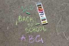 Dra tillbaka till skolan suckar skriftligt med kulöra chalks på en trottoar Dra tillbaka till skolan på en asfalt och semesterbeg Royaltyfria Bilder