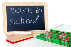 Dra tillbaka till skolan: svart tavla kritiserar och bunten av böcker Royaltyfria Foton