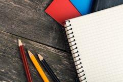 Dra tillbaka till skolan, tillförsel, anteckningsbok på den gråa bakgrunden Arkivbild