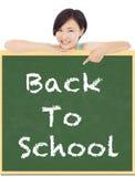 Dra tillbaka till skolan, ung studentflickapunkt till svart tavla Fotografering för Bildbyråer