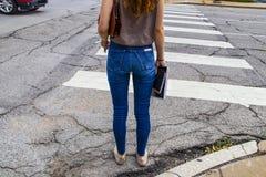 Dra tillbaka till skolan - Unidentifiable baksida av iklädd jeans för flickan med långt rött håranseende på övergångsstället med  royaltyfri foto