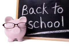 Dra tillbaka till skolapåminnelsen, piggybank, svart tavla, begrepp för utbildningskostnader Royaltyfri Fotografi