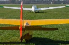 Dra upp en glidflygplan vid ett motoriserat flygplan Arkivbild