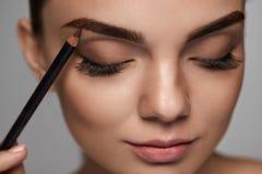Dra upp konturerna av för ögonbryn Härlig kvinna med den bruna ögonbrynblyertspennan royaltyfri fotografi