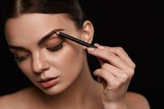 Dra upp konturerna av för ögonbryn Härlig kvinna med den bruna ögonbrynblyertspennan Arkivfoton