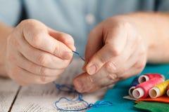 Draad in de naald Close-up van de mens die draad trekken in Stock Foto