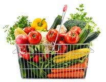 Draad het winkelen mand met kruidenierswinkels op wit Stock Foto's