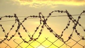 Draad metaalgrens bij zonsondergang, grensstreek, veiligheidsgrondgebied stock video