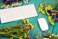 Draadloos slank toetsenbord, muis en kleurrijke bloemen op blauwe woode royalty-vrije stock afbeelding