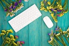 Draadloos slank toetsenbord, muis en kleurrijke bloemen op blauwe woode royalty-vrije stock afbeeldingen