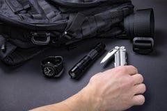 Draag EDC elke dag punten voor mensen in zwarte kleur - rugzak, tactische riem, flitslicht, horloge en verzilver multihulpmiddel stock foto
