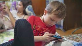 Draagbare console Sluit omhoog van gezichtsjongen van 8 jaar de oude jong geitje het spelen van computerspelen draagbare console stock video