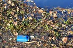 Draagstoel en afval op waterweg Stock Fotografie