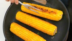 Draai de gekookte maïskolven in een pan stock video