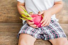 Draakfruit op jongens` s handen op een houten achtergrond Royalty-vrije Stock Afbeelding