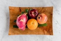Draakfruit of Pitaya, appelen, granaatappels en sinaasappelen in een houten schotel Stock Afbeelding