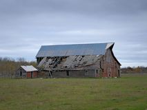 Drab Abandoned Dilapidated Farm Barn and Shed with clouds. In northern Minnesota stock photos