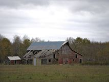 Drab Abandoned Dilapidated Farm Barn and Shed with clouds. In northern Minnesota royalty free stock images