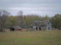 Drab Abandoned Dilapidated Farm House and Shed with clouds. In northern Minnesota stock photography