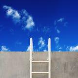 Drabina na betonowej ścianie i niebieskim niebie fotografia royalty free
