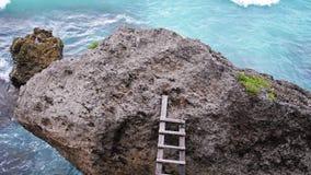 Drabina nad kamienną skałą z oceanem w tle swobodny ruch 3840x2160 zbiory wideo