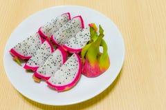 Drachefrucht (Pitaya) auf Teller mit hölzernem Hintergrund Stockbilder