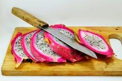 Drachefrucht und -messer auf Hackklotz Stockbilder
