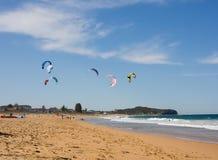 Drachen, der am Strand surft Lizenzfreies Stockbild