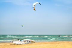 Drachen, der in windigen Strand mit Windsurfer surft Lizenzfreie Stockfotografie