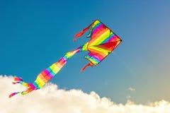 Drachen fliegt in den Wind im sonnigen Licht und im etwas bewölkten Himmel im Hintergrund lizenzfreie stockfotografie