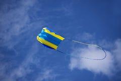 Drachen-, Gelbes und Blauesfliegen im Wind gegen den Himmel mit Wolken, k Lizenzfreies Stockbild